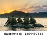 Special forces men in camouflage uniforms paddling army kayak. Boat moving across the river in the morning, diversionary mission,copy space. - Image - stock photo