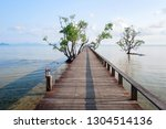 wooden bridge on the beach into ... | Shutterstock . vector #1304514136