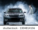 A car washer washes a gray car with a high-pressure washer at night on the street. Expensive advertising photography - stock photo