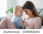 young mother  holding her sick... | Shutterstock . vector #1305083650