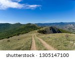 dirt road on top of a mountain... | Shutterstock . vector #1305147100