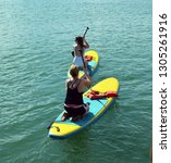 two young women paddle boarders ...   Shutterstock . vector #1305261916