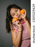 Small photo of Close up portrait head shot of a young, beautiful and attractive Chinese Asian girl wearing a traditional Chinese dress (cheongsam) in a studio. She is holding two oranges and smiling cheekily.