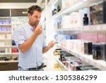 elegant man choosing perfume in ... | Shutterstock . vector #1305386299
