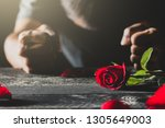 red roses on a black table top... | Shutterstock . vector #1305649003
