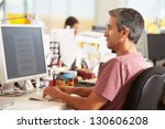 man working at desk in busy... | Shutterstock . vector #130606208