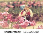 Two kissing dolls in pink tulip garden. - stock photo