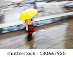 picture in motion blur of a woman with a yellow umbrella on the move in the city - stock photo