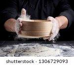 man sifts white wheat flour... | Shutterstock . vector #1306729093