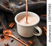 Small photo of Pouring tasty hot cocoa drink into retro mug with ingredients: cinnamon, anise and cove on black concrete table. Winter drink. Rustic look. Copy space for text. Square crop.