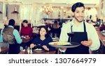 portrait of male waiter who is... | Shutterstock . vector #1307664979