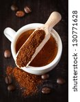 Cup of coffee and scoop with ground coffee beans. - stock photo