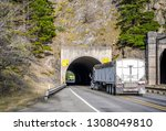 Two big rig commercial long haul semi trucks transporting cargo in semi trailers running through the tunnel towards each other on the narrow road along the Columbia River in Columbia River Gorge