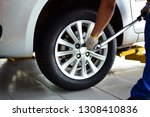 Small photo of a mechanic in blue uniform with white glove holding a pound wrench tighten the bolts of the wheel