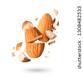 Flying in air fresh raw whole and cut almonds  isolated on white background. Concept of Almonds is torn to pieces close-up. High resolution image