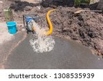 Small photo of Plumbing pumping water out of excavated earthwork trench of broken main water pipe in residential road area with portable motor pump draining damage.