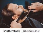 barber cuts his beard to man in ... | Shutterstock . vector #1308538510