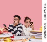 Photo of astonished woman and man sit back to each other, hold modern cell phones, recieve shocking notification, analyse papers with charts, stare in bewilderment, isolated over pink background