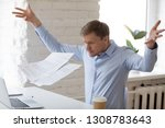 Small photo of Angry mad businessman sitting at workplace throwing documents paper feels nervous unable control emotions and handle the stress at work. Bad day, problems in business huge debts and bankruptcy concept
