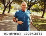 Cheerful senior man jogging in...