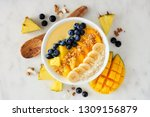 Healthy pineapple, mango smoothie bowl with coconut, bananas, blueberries and granola. Above view scene on a bright background.