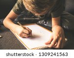 Small photo of Close up bottom view of a young boy drawing a face on a white sheet. Kid hold a pencil and draw something, warm orange light at home. Children writing on a paper. Teen drawing sitting on a sofa