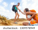 people hiking man helping woman ... | Shutterstock . vector #1309578949