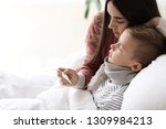 mother taking care of his son... | Shutterstock . vector #1309984213