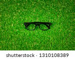 eyeglasses over green grass... | Shutterstock . vector #1310108389
