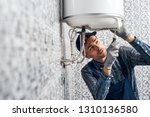 Small photo of Almost done. Worker set up electric heating boiler at home. Close-up of young handyman