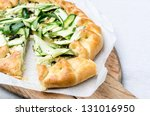 Healthy baked zucchini galette tart for lunch on rustic wooden serving platter - stock photo