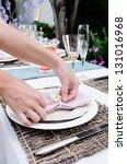 Close up of party planners hands tying ribbon on napkins to outdoor entertaining table setting in the garden - stock photo