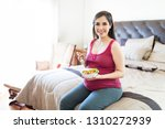 pregnant woman eating fresh... | Shutterstock . vector #1310272939