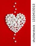small white pills goes through... | Shutterstock . vector #1310415013