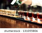 Stock photo bartender pours alcoholic drink into small glasses on bar 131055806