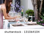 Hostess bringing water jug to the table set for a garden party - stock photo
