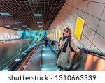 beautiful woman uses escalator... | Shutterstock . vector #1310663339
