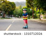 child on kick scooter in park....   Shutterstock . vector #1310712026