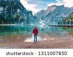 woman in red jacket is standing ... | Shutterstock . vector #1311007850