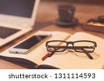 glasses and laptop on the table ... | Shutterstock . vector #1311114593