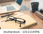 glasses and laptop on the table ... | Shutterstock . vector #1311114596