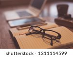 glasses and laptop on the table ... | Shutterstock . vector #1311114599