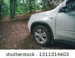 white suv car at forest trail... | Shutterstock . vector #1311314603