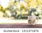 cup coffee and sunny trees... | Shutterstock . vector #1311371876