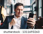 excited young businessman... | Shutterstock . vector #1311693263