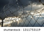 barbed wire fence with dramatic ... | Shutterstock . vector #1311753119