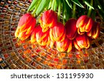 Red tulips  on mosaic table with reflection. - stock photo