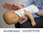 Small photo of Back blows (the Heimlich maneuver or Heimlich manoeuvre) on a simulation mannequin infant dummy during medical training Basic Life Support
