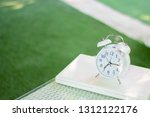 White Alarm Clock And Laptop O...