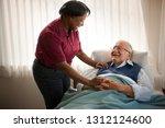 happy female nurse comforting... | Shutterstock . vector #1312124600